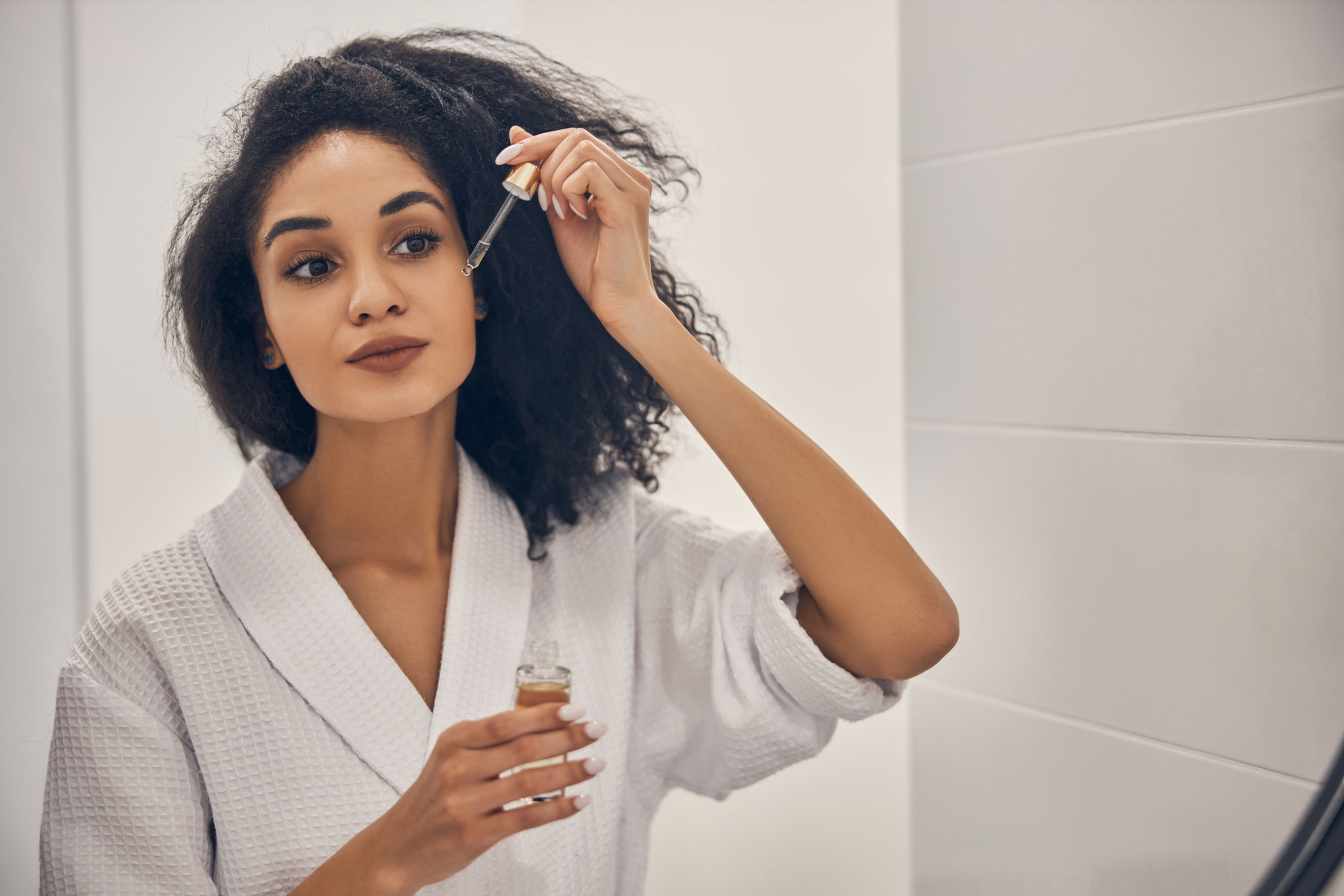 Mulher em frente ao espelho aplicando sérum no rosto com um conta-gotas