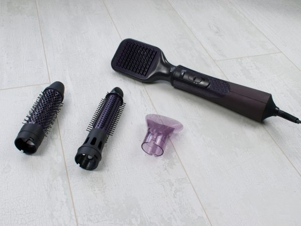 Isolated on wood background hairdryer and nozzles: volume diffuser, massage, round combs and styling concentrator for focused airflow.