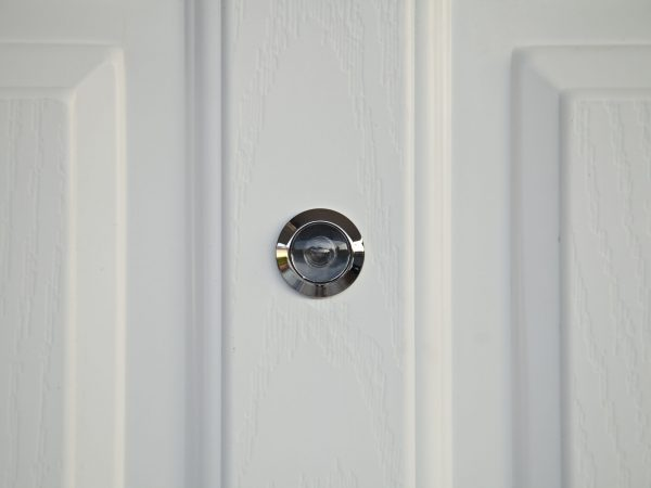 17253341 – door lens peephole on white wooden texture
