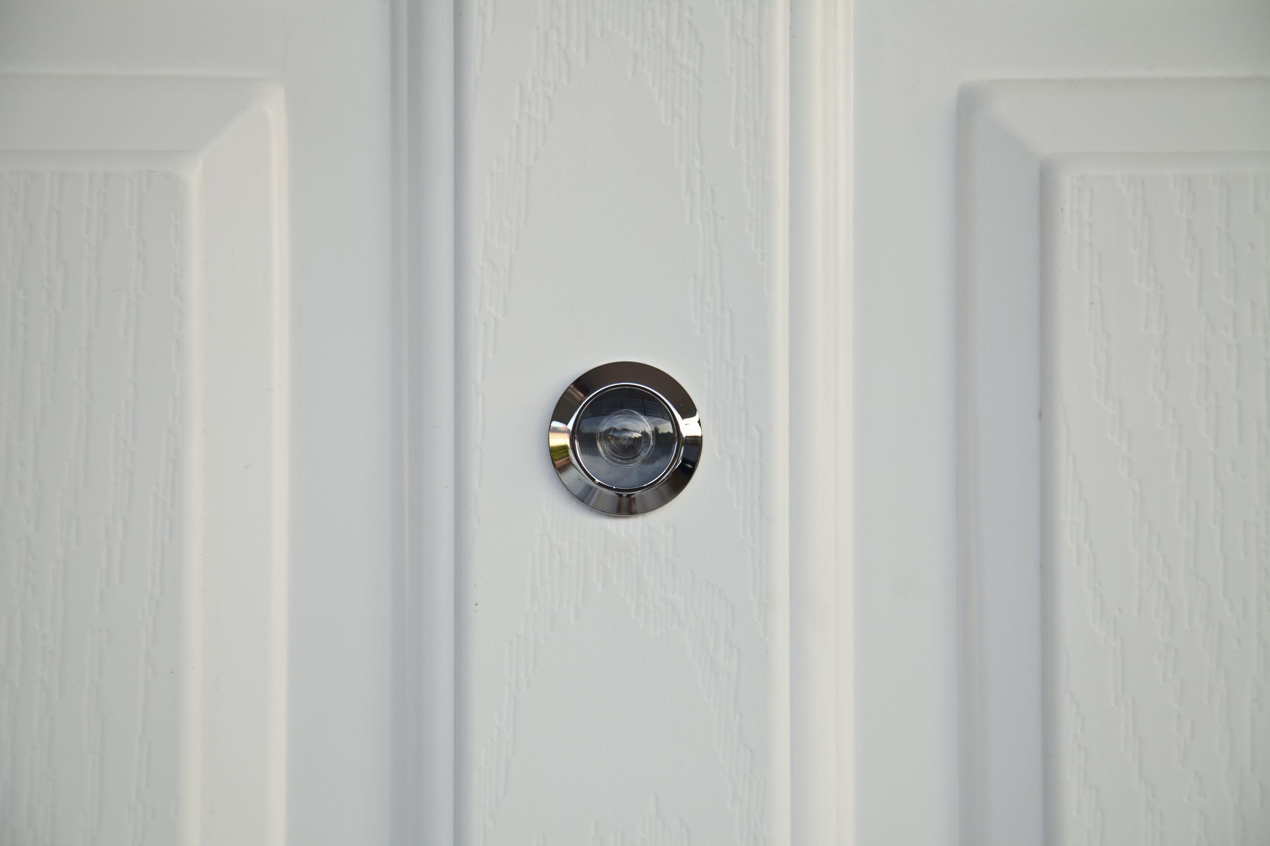 Parte de uma porta branca com olho mágico