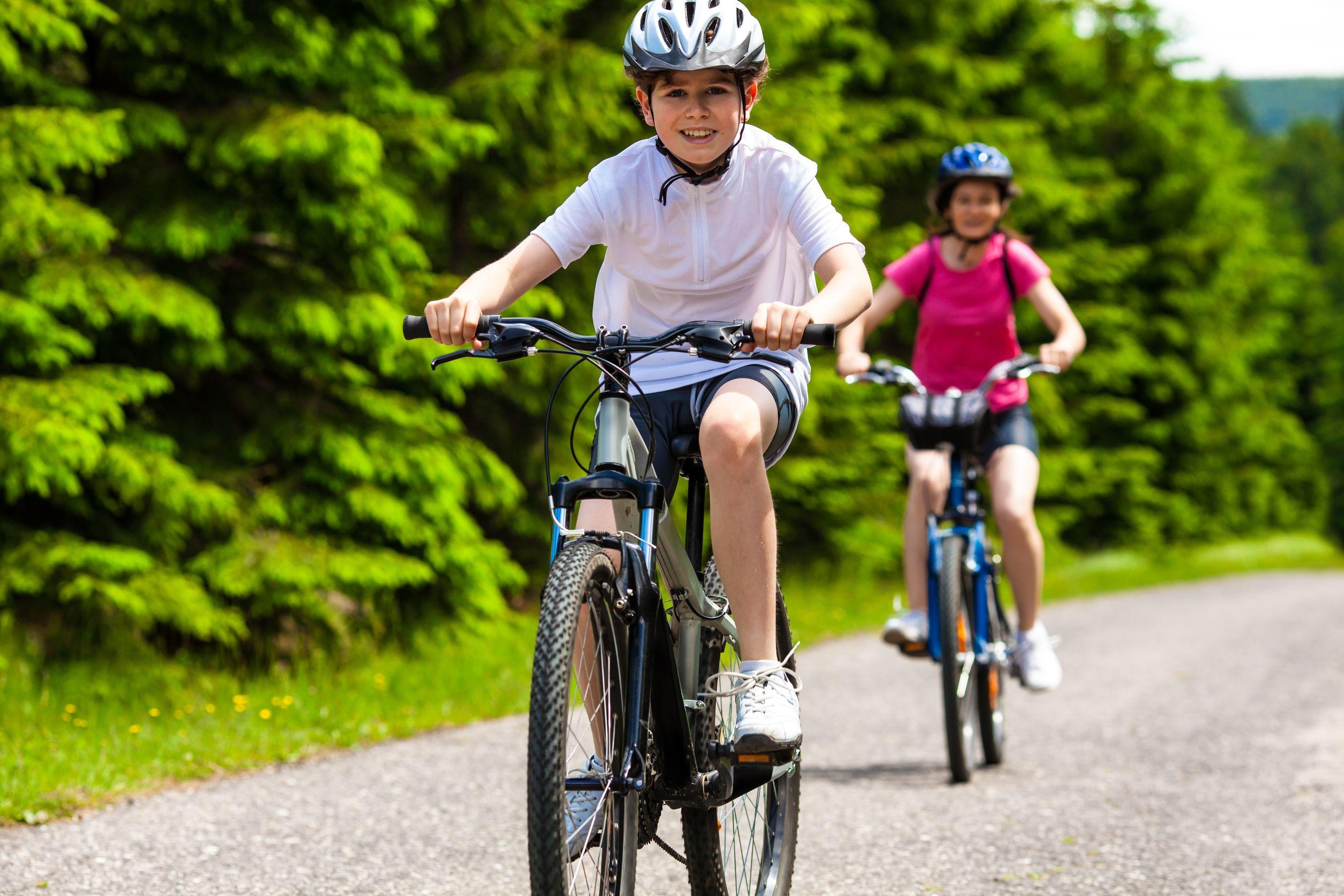 crianças pedalando com roupa de ciclismo