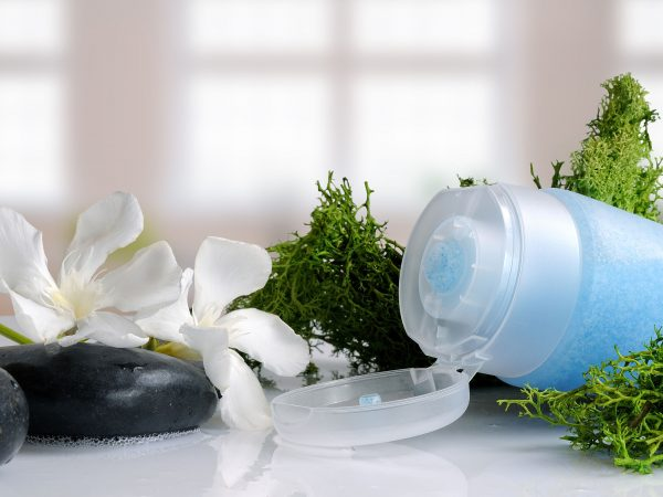 Blue exfoliating gel with seaweed on a white glass table in a bath
