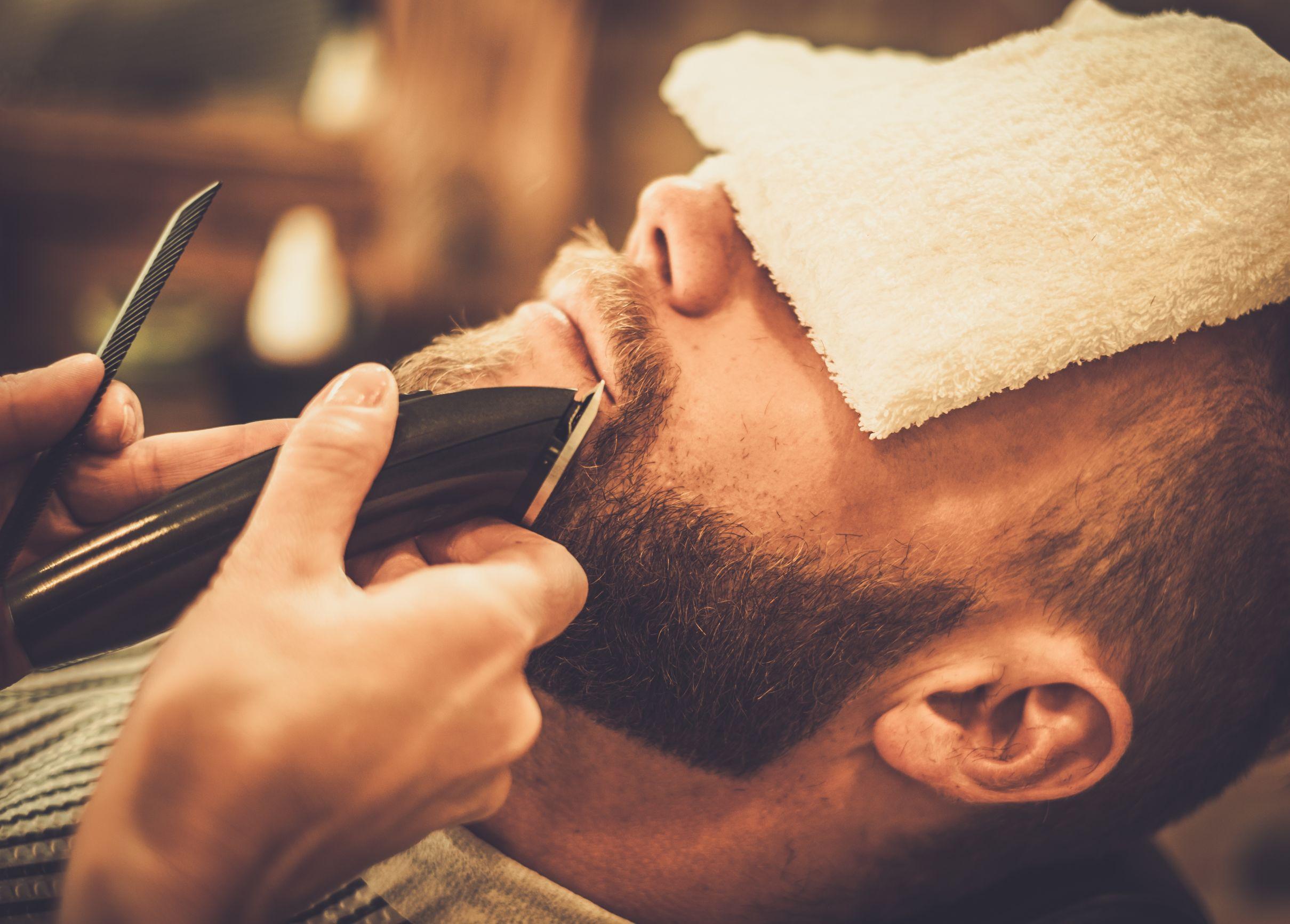 Barbeiro passando a máquina na barba de um homem