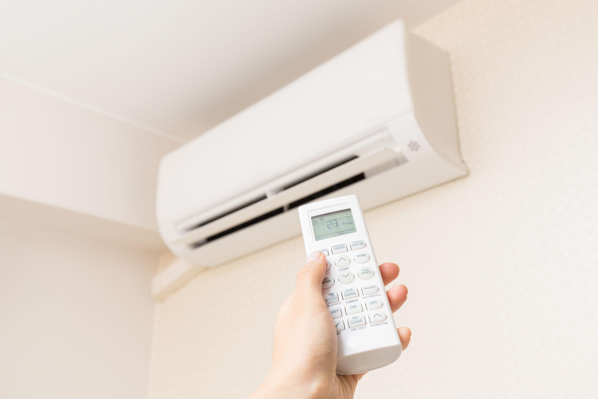 Pessoa ligando ar condicionado com controle remoto