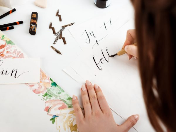 Girl writing calligraphy on postcards. Art design. Copy space.