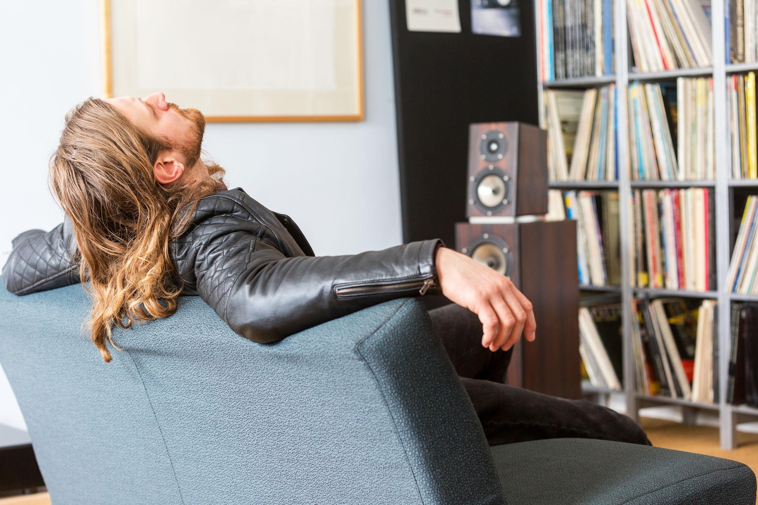 Um homem recostado em um sofá ouvindo música
