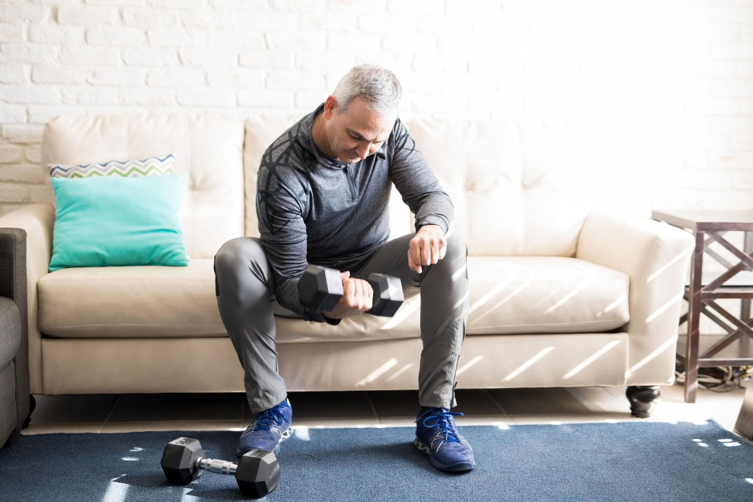 homem praticando exercícios de academia em casa.