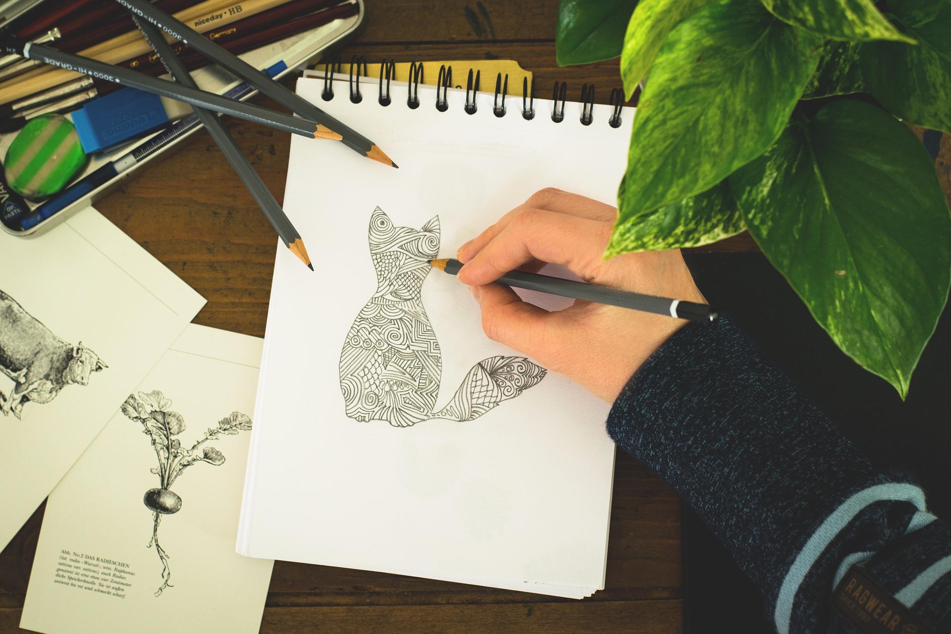 Mão desenhando em caderno com espiral.