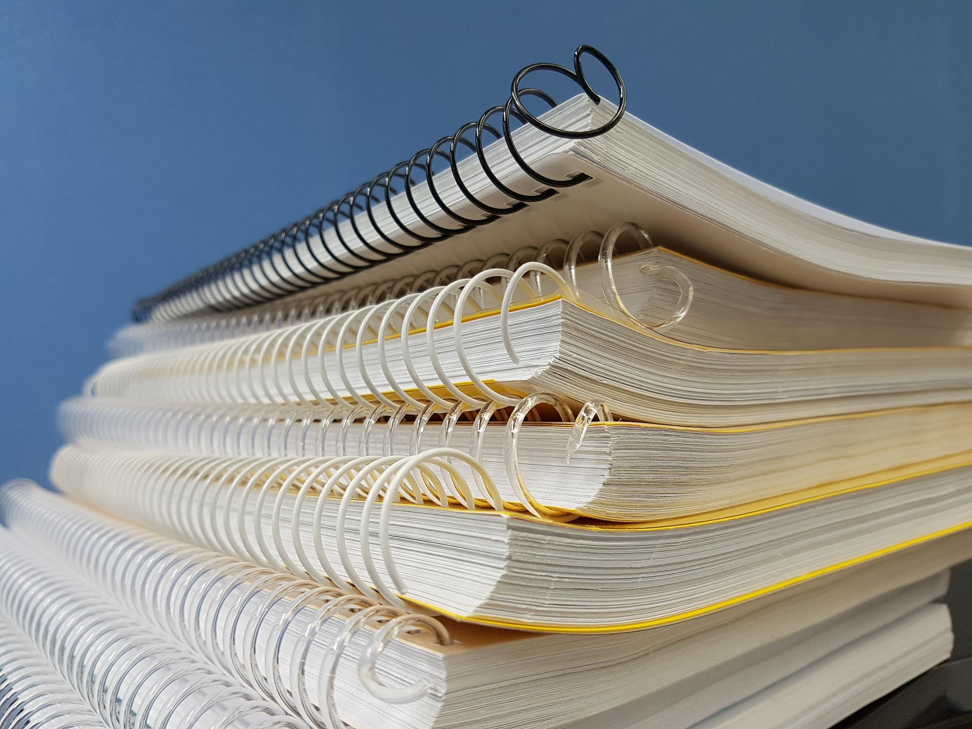Vários cadernos com espiral empilhados.