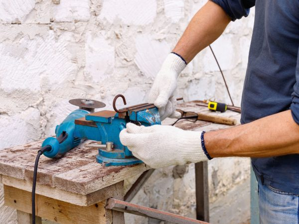 Worker makes repairs  with electric tools  hammer and  pliers in backyard of  house in outdoor.  Hand with brush closeup