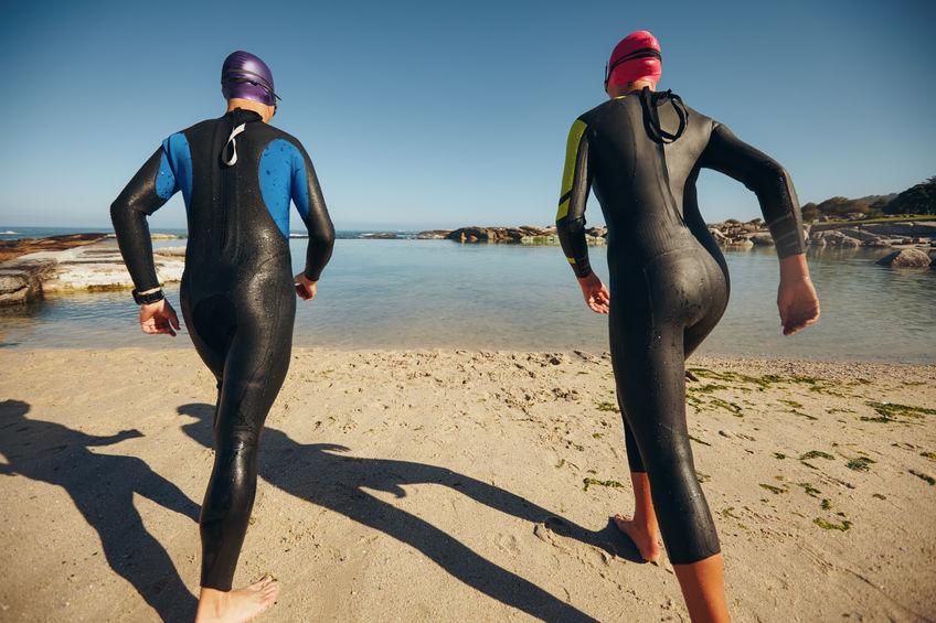 Homem e mulher com roupa de mergulho correndo em direção ao mar