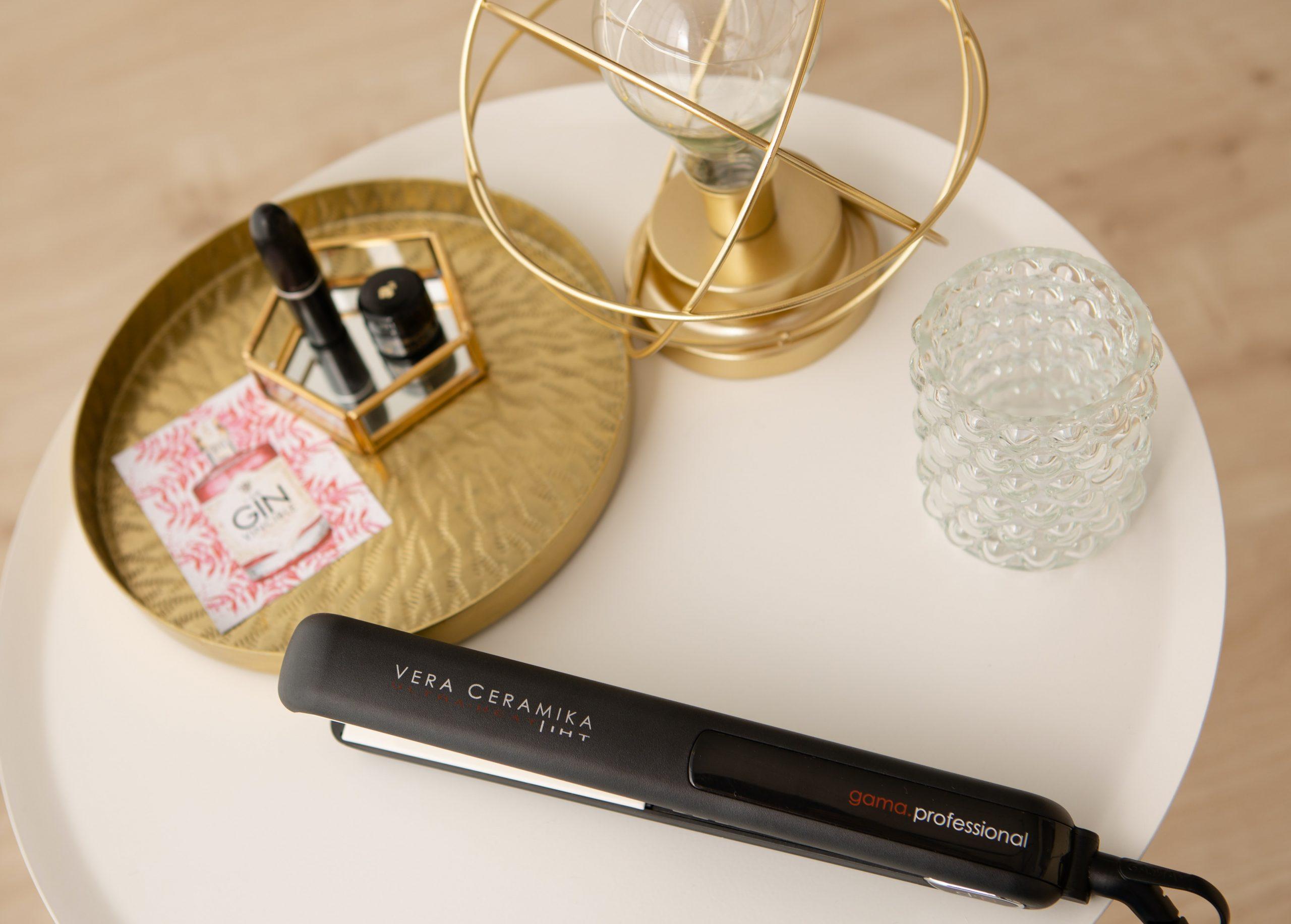chapinha preta em cima de uma mesinha com batons e luminária ao lado