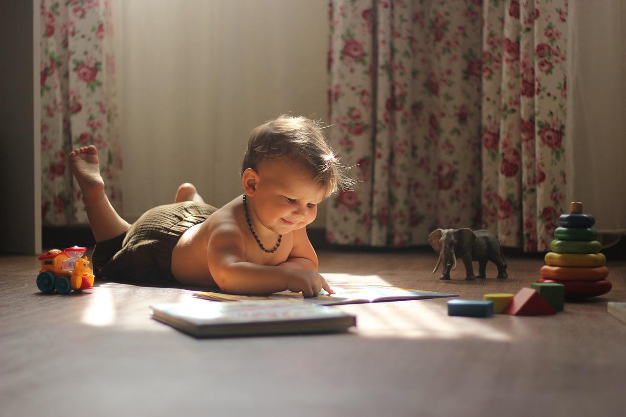 Criança deitada no chão, olhando livro, com brinquedos educativos ao redor dela.