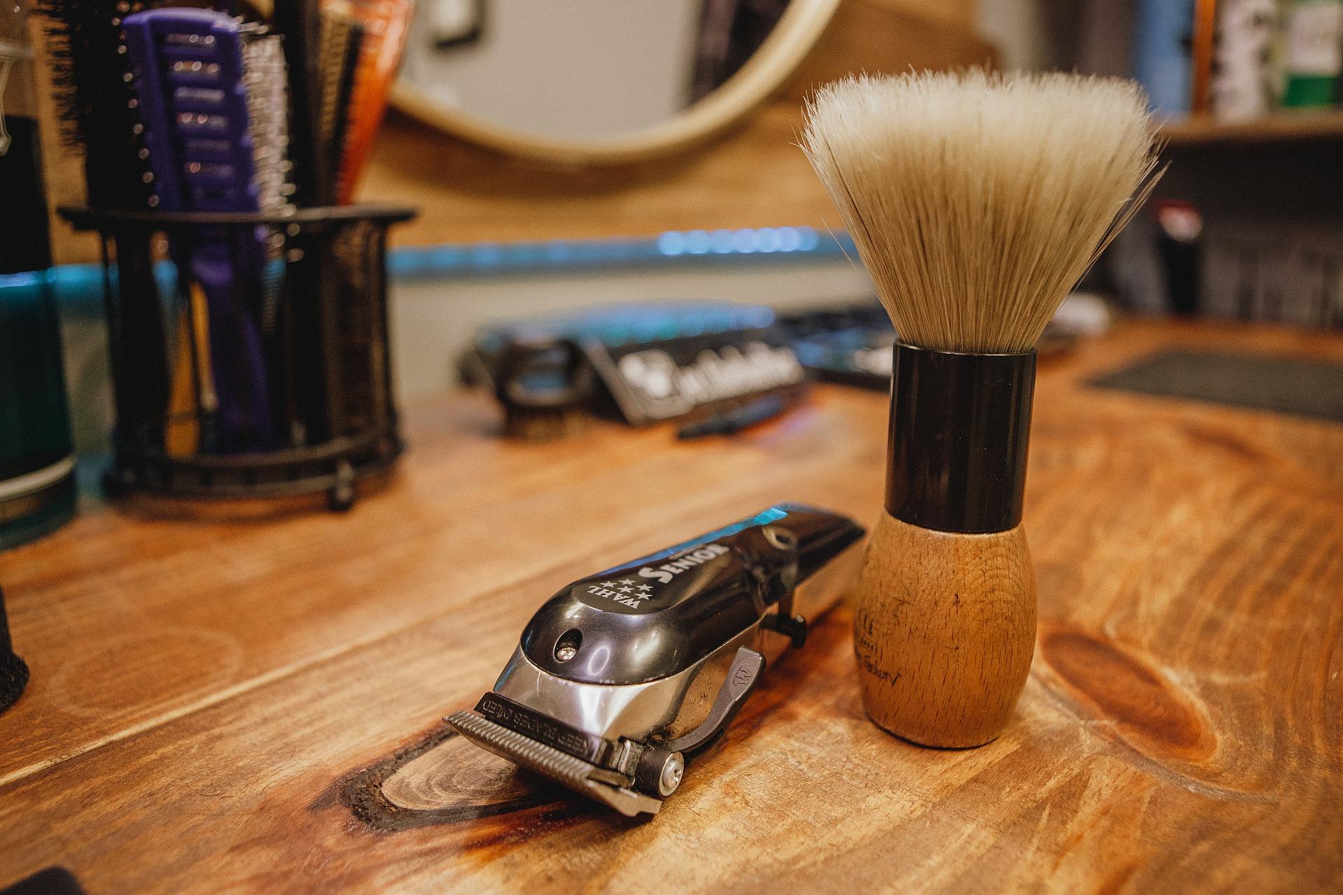 Um aparador e um pincel de barba em uma mesa de madeira