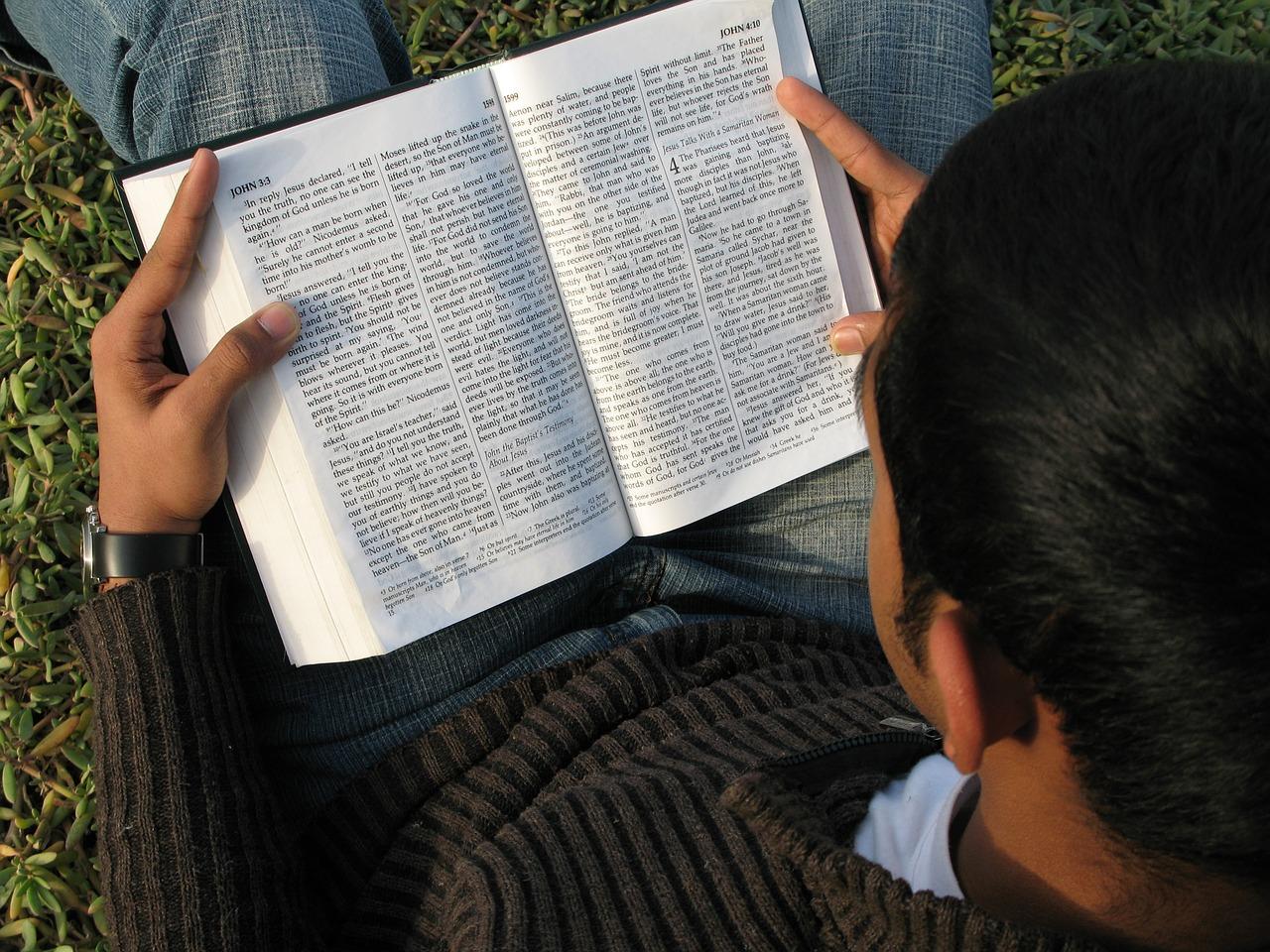 Homem sentado lendo a bíblia.