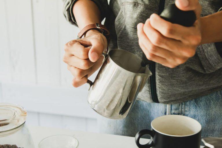 Homem espumando leite na jarra.