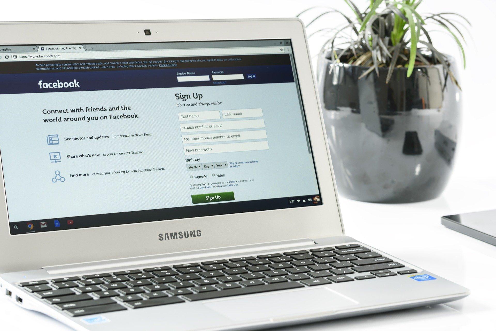 Notebook da Samsung, aberto no Facebook, em uma mesa ao lado de uma planta