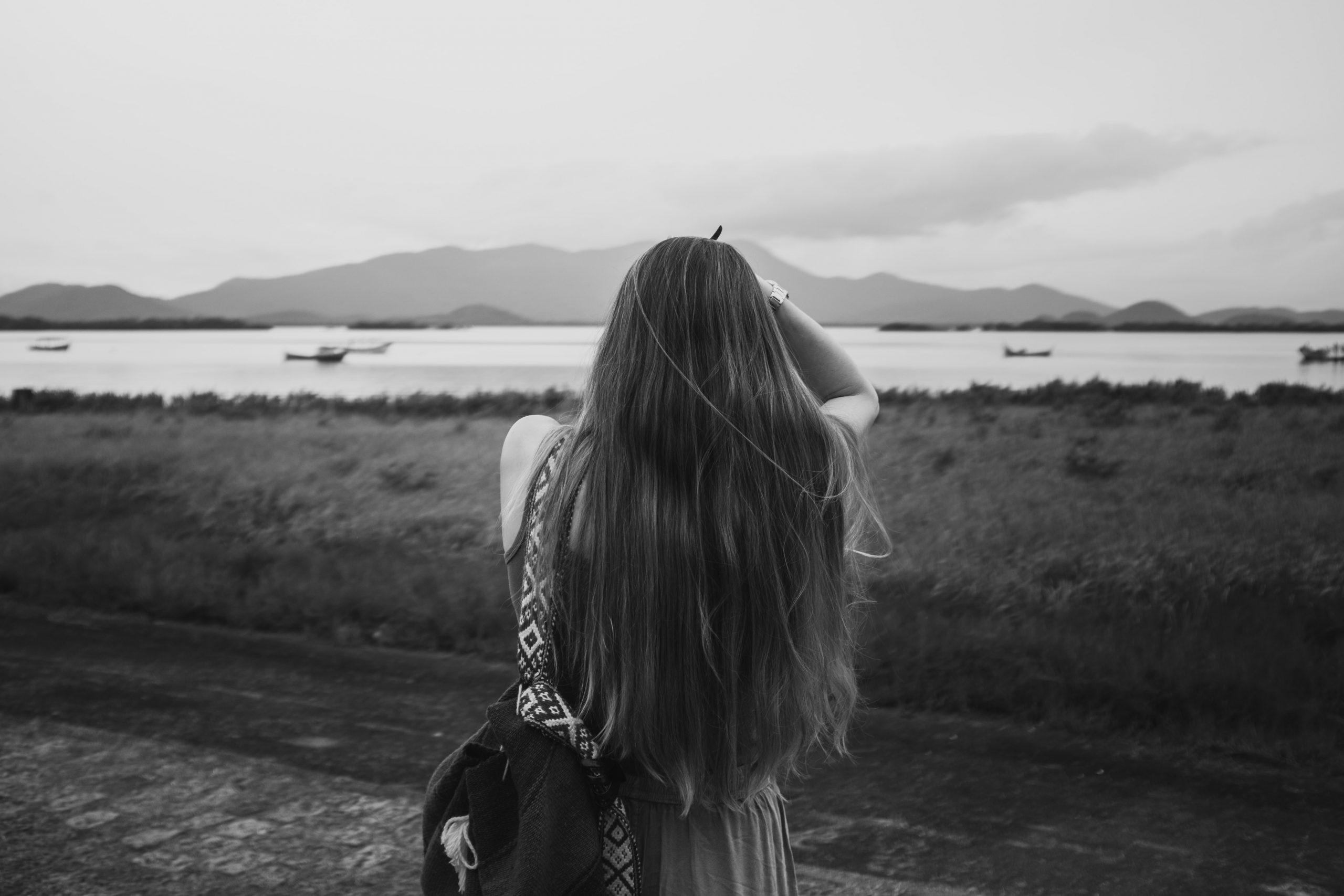 mulher de cabelo longo e liso virada de costas para a câmera