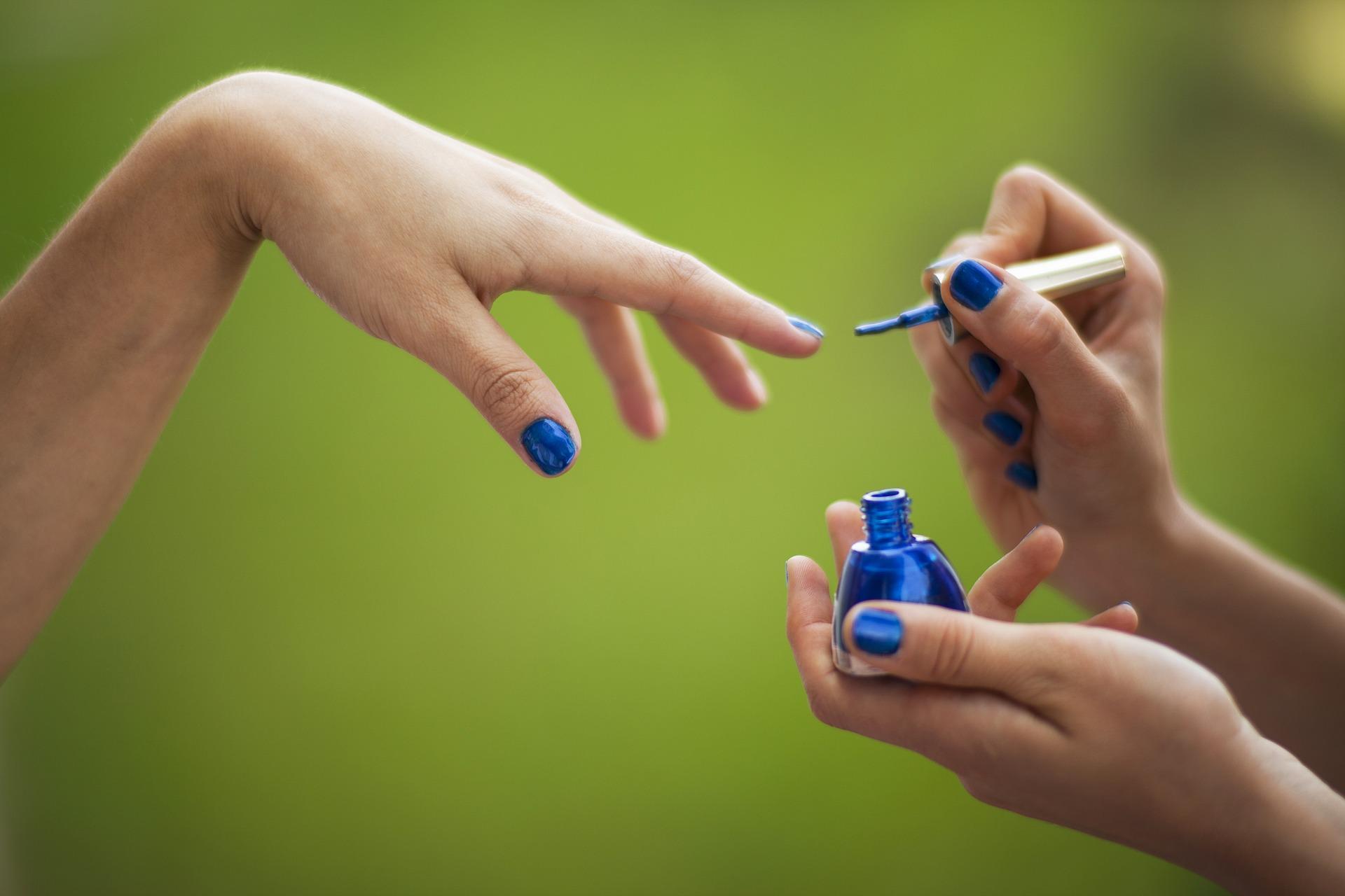 Manicure pintando as unhas de uma cliente com esmalte azul.