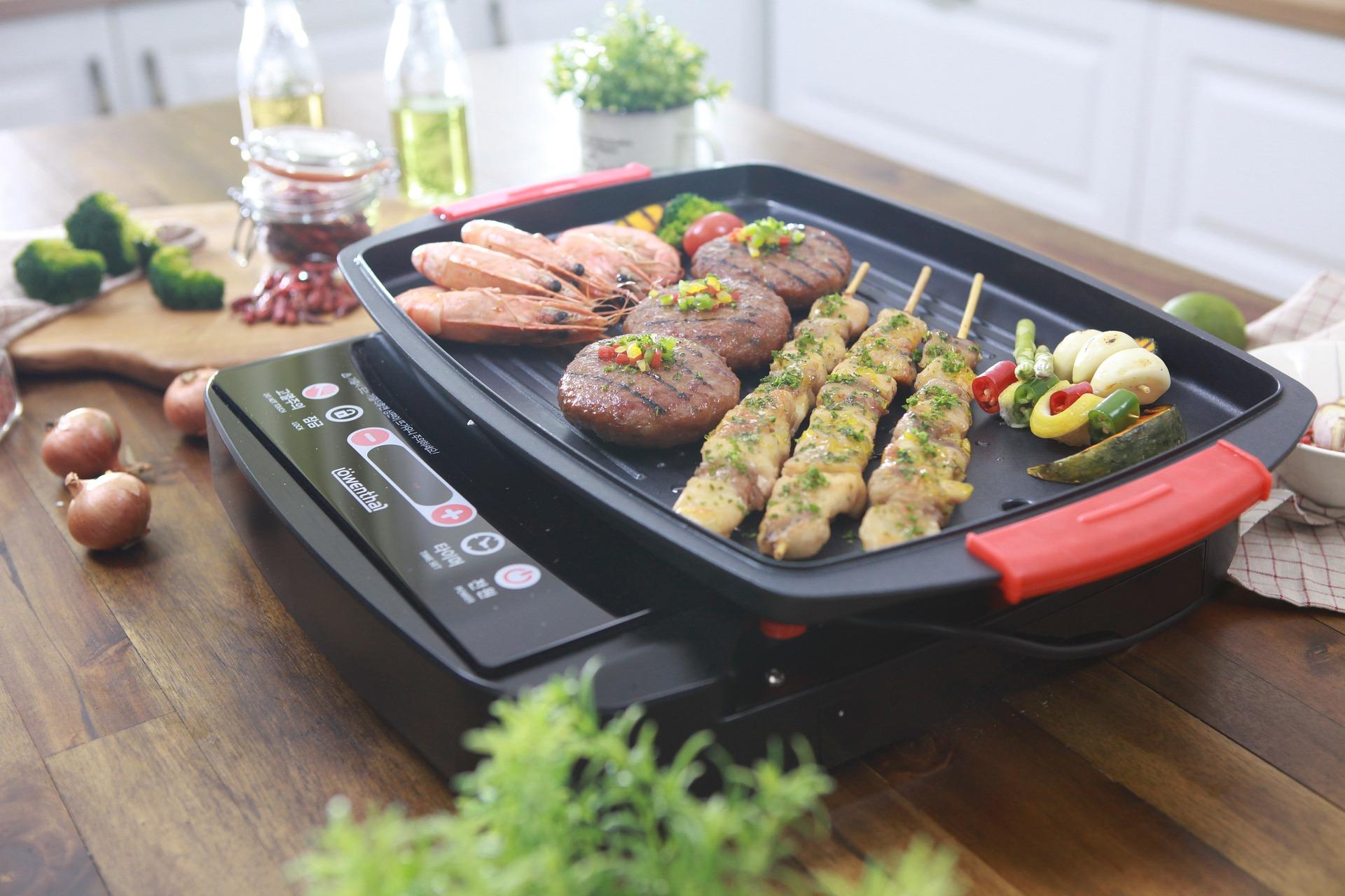 Grill elétrico em uma mesa de madeira sendo usado para a preparação de legumes, carnes e frutos do mar.