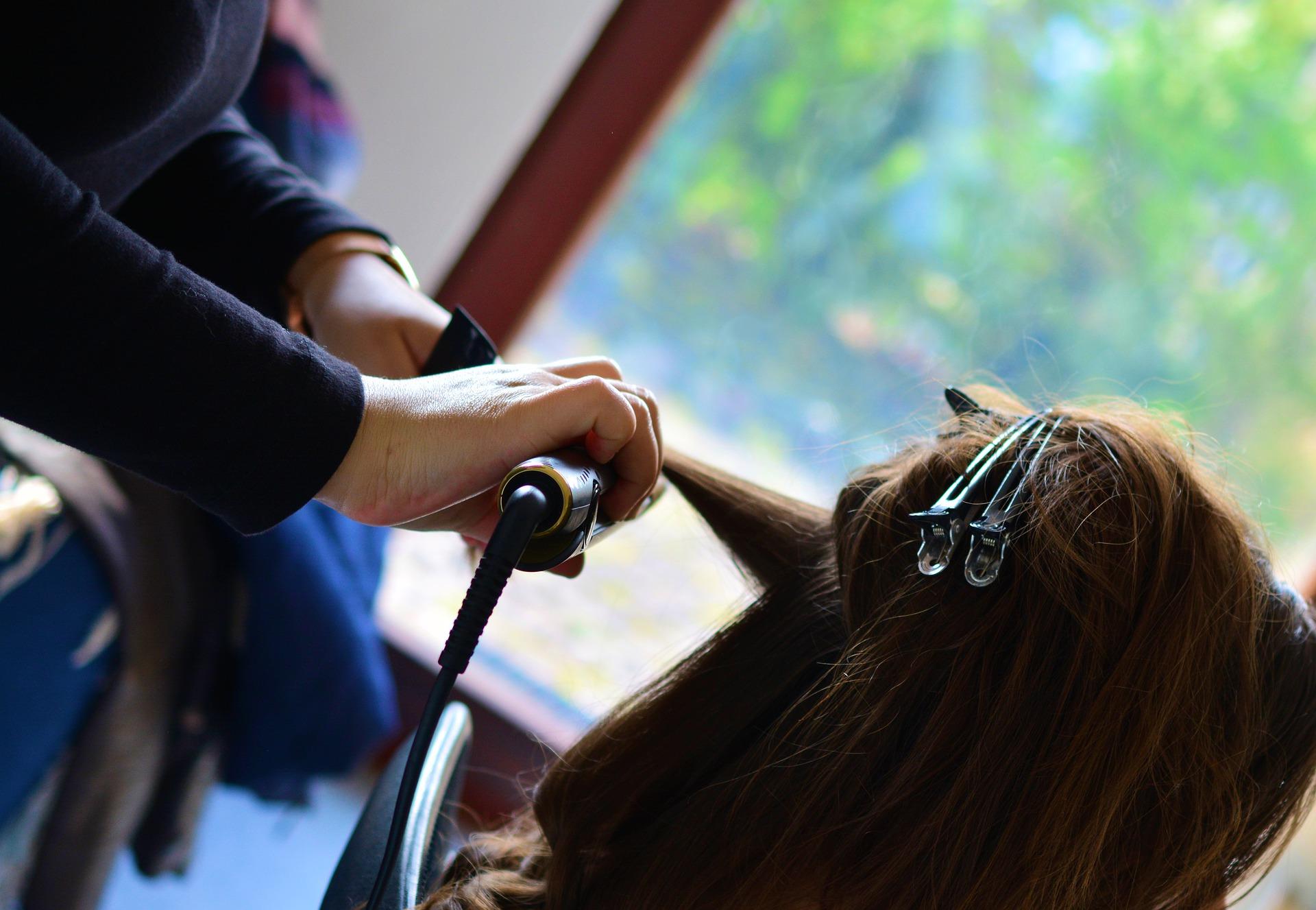 cabeleireira alisando o cabelo de uma mulher com chapinha
