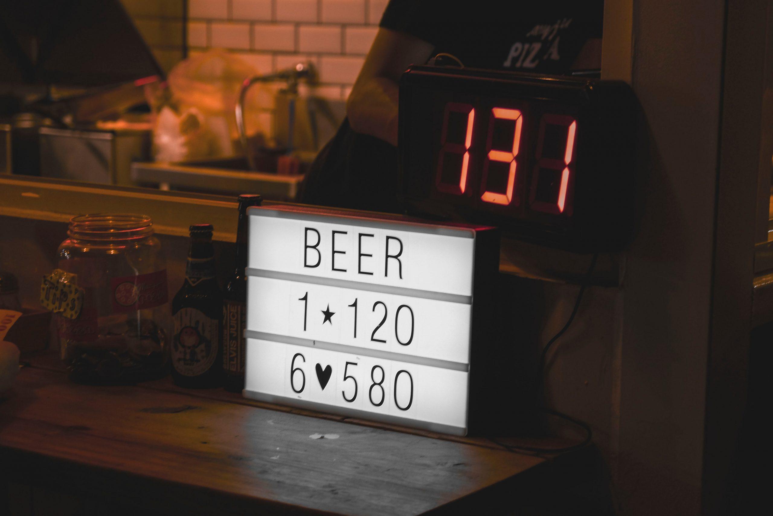 Bancada de uma cozinha com um rádio relógio ligado, marcando a hora, além de outros itens como letreiro decorativo em LED, garrafas e um pote de vidro.