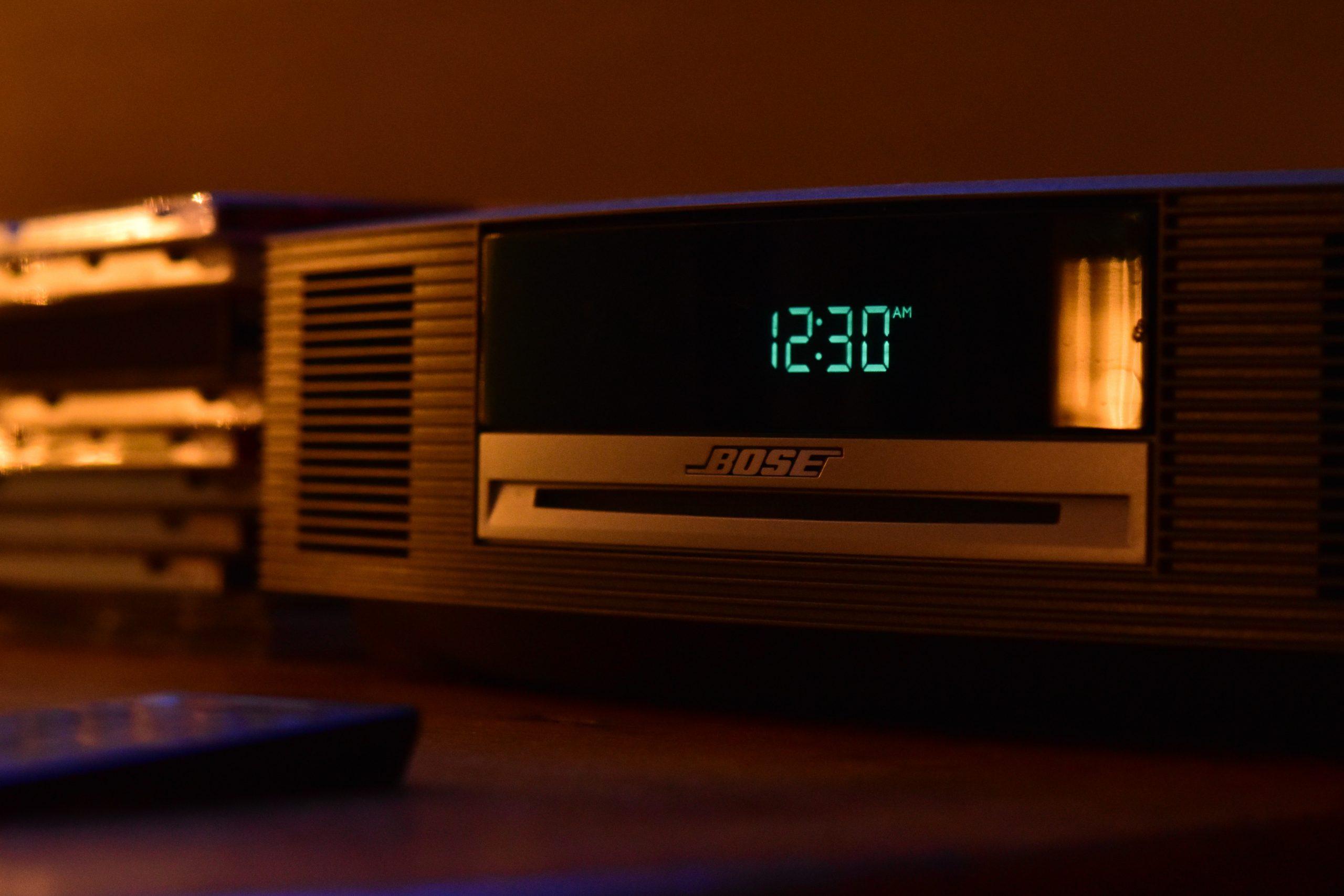 Rádio prata em uma mesa com o visor mostrando a hora