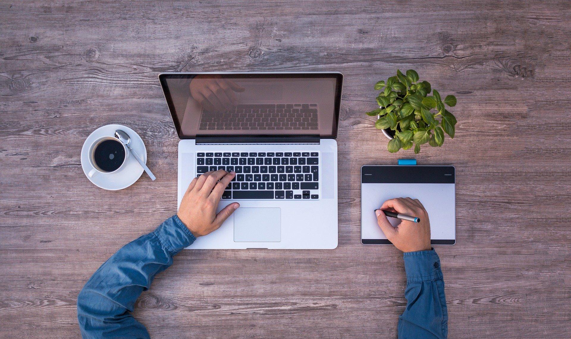 Homem, notebook e mesa digitalizadora.