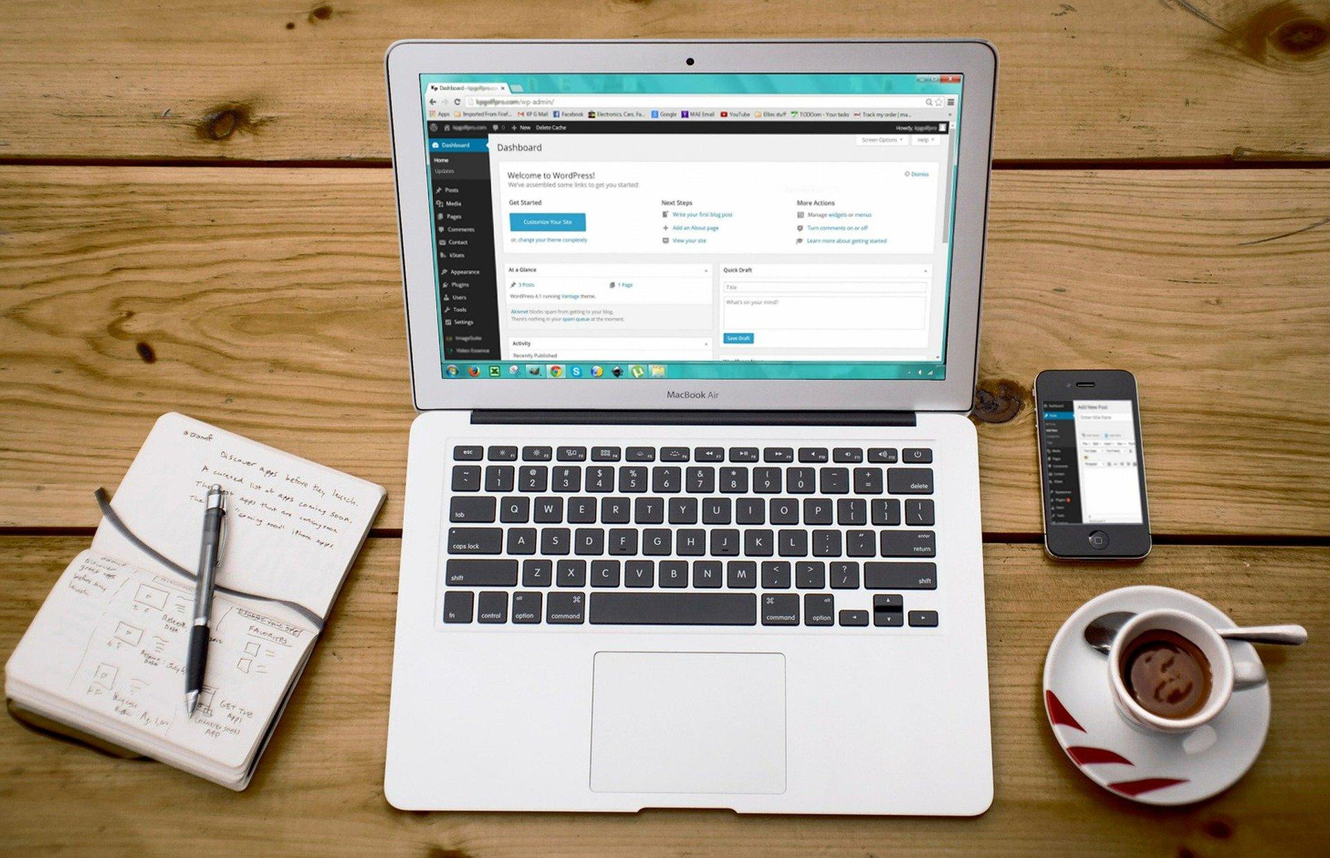 Notebook com WordPress na tela, caderno de anotações, celular e xícara de café ao lado.