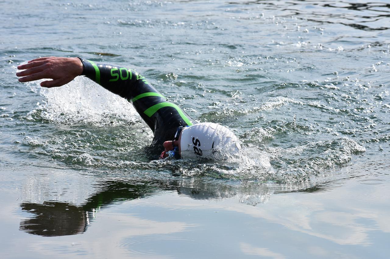 Homem com roupa de neoprene nadando