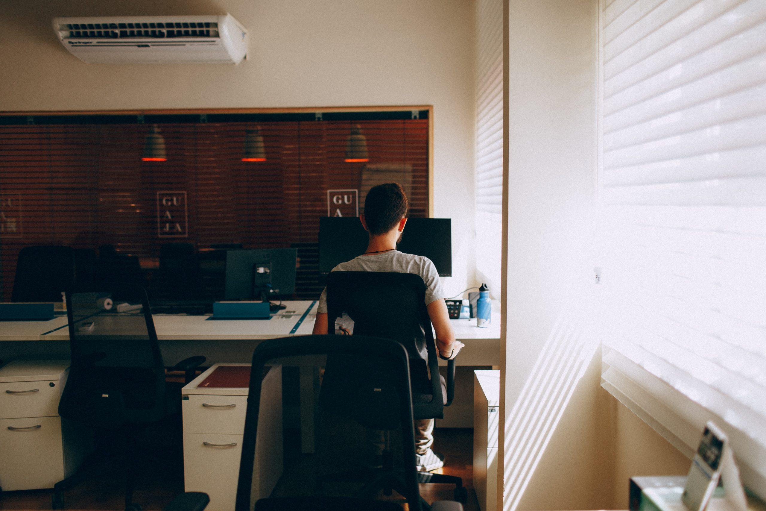 Menino de costas mexendo no computador em um escritório