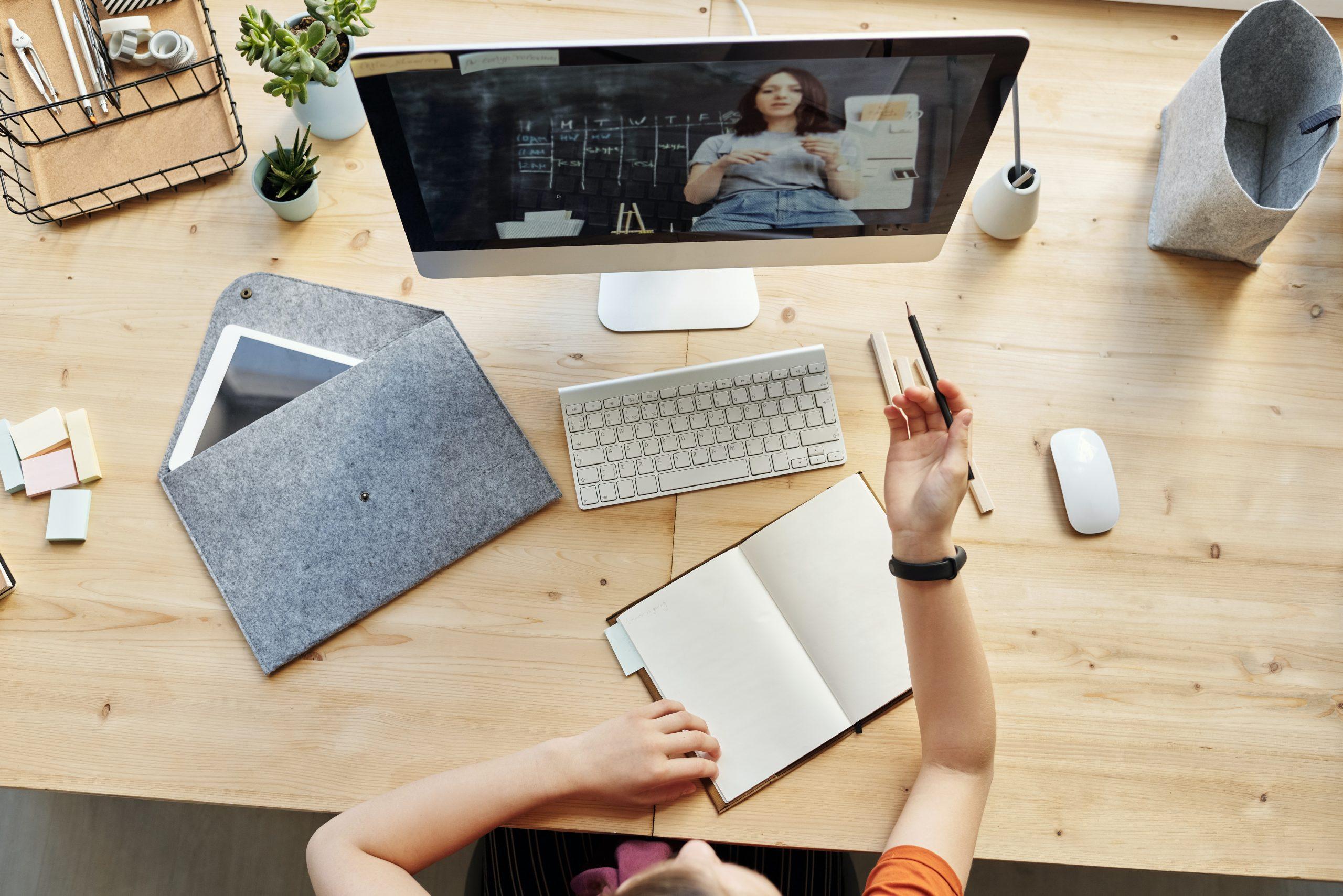 Pessoa na mesa de estudos assistindo videoaula na tela do computador