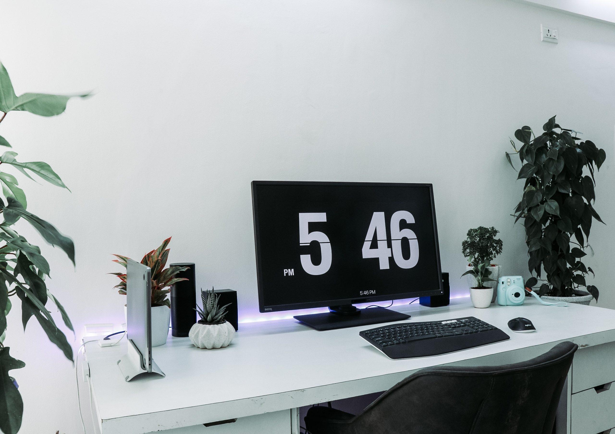 Computador mostrando o horário em um espaço de home office com plantas