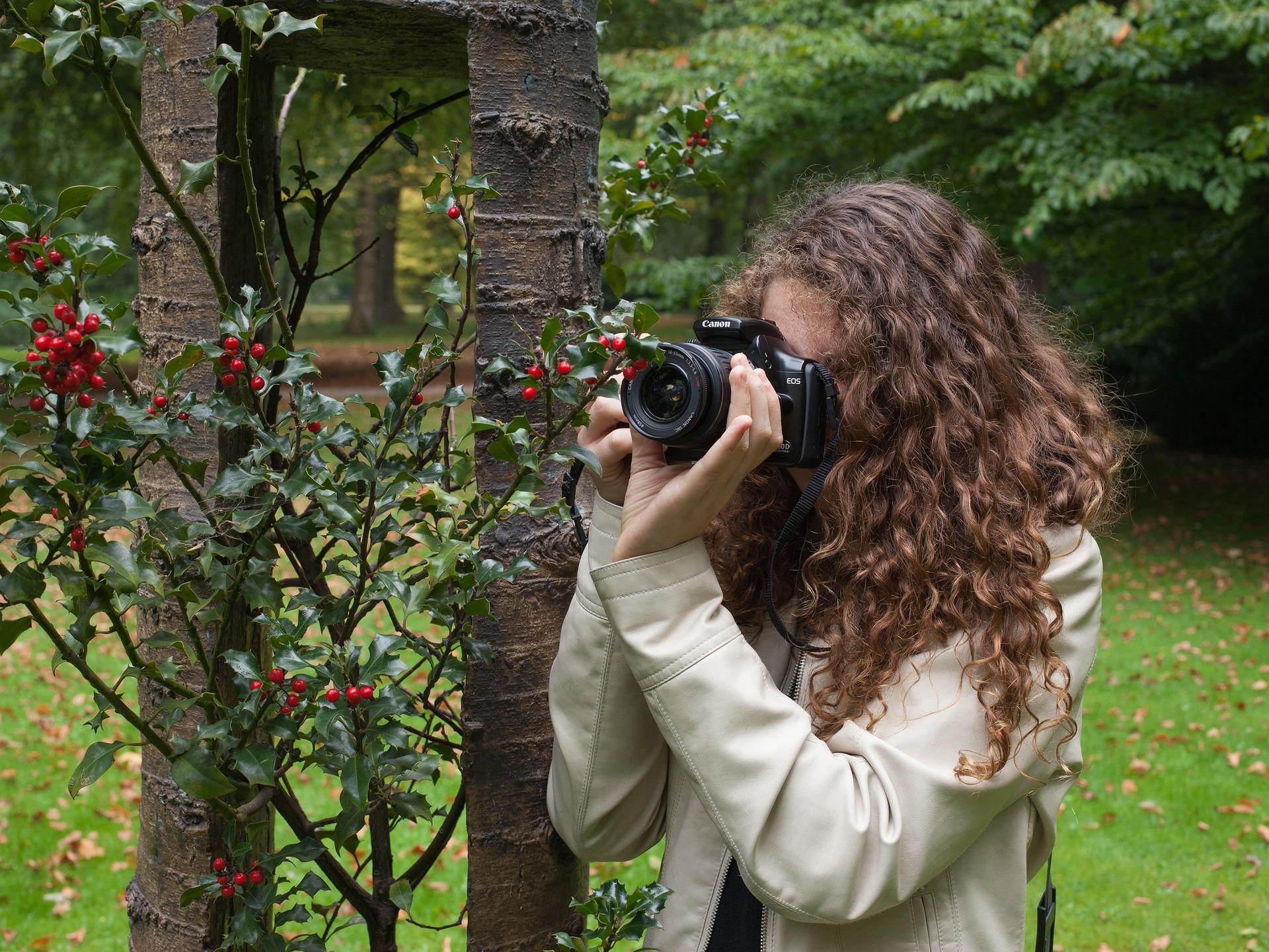 Mulher fotografando detalhe de fruto de uma árvore.