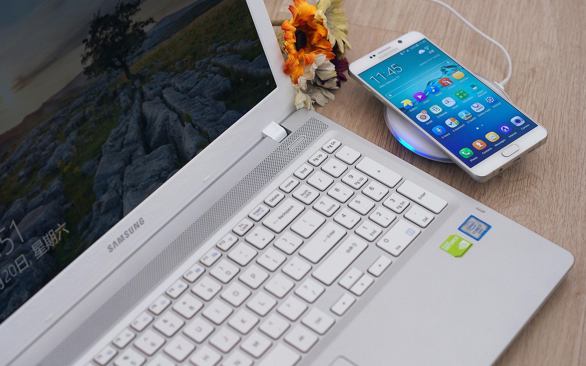 Notebook e celular da marca Samsung em uma mesa de madeira