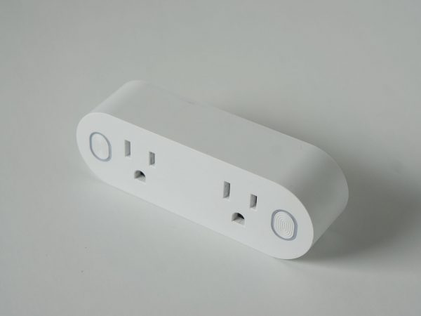 This double smart WIFI plug outlet can switch an electric device on or off via wi-fi. Isolated on a horizontal white background with copyspace or empty room space for text or copy.