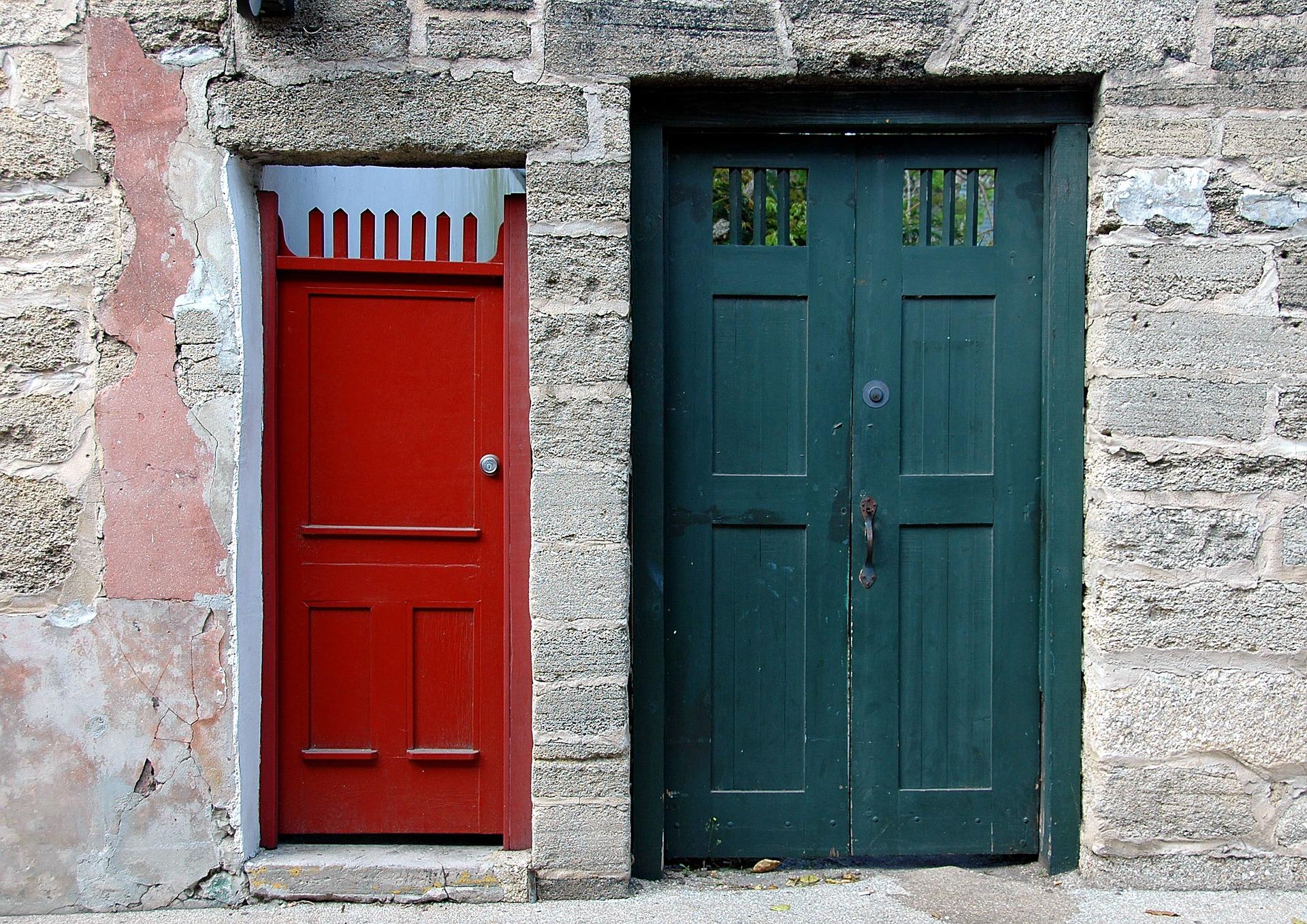 Frente de uma casa com um portão vermelho e outro verde
