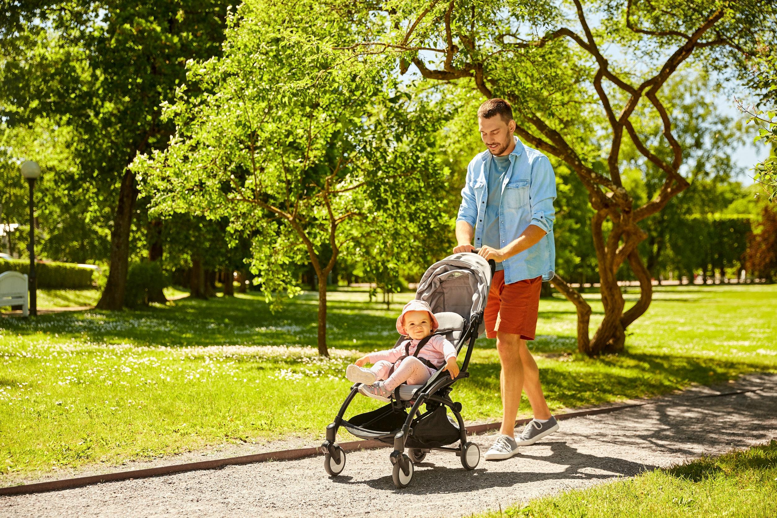 pai feliz com filho em carrinho de bebé no parque de Verão
