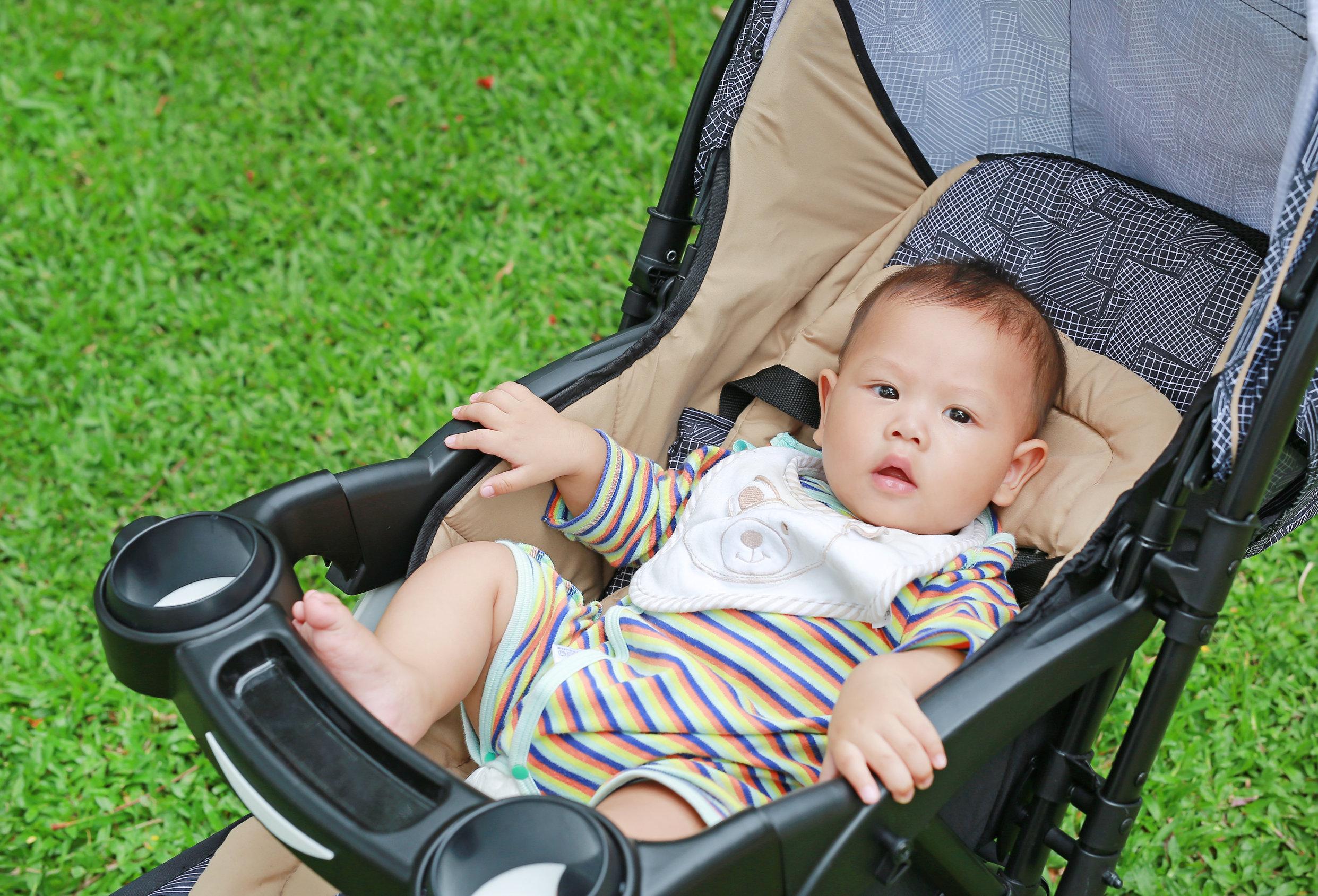 Menino de 6 meses sentado no carrinho de bebé no jardim verde.