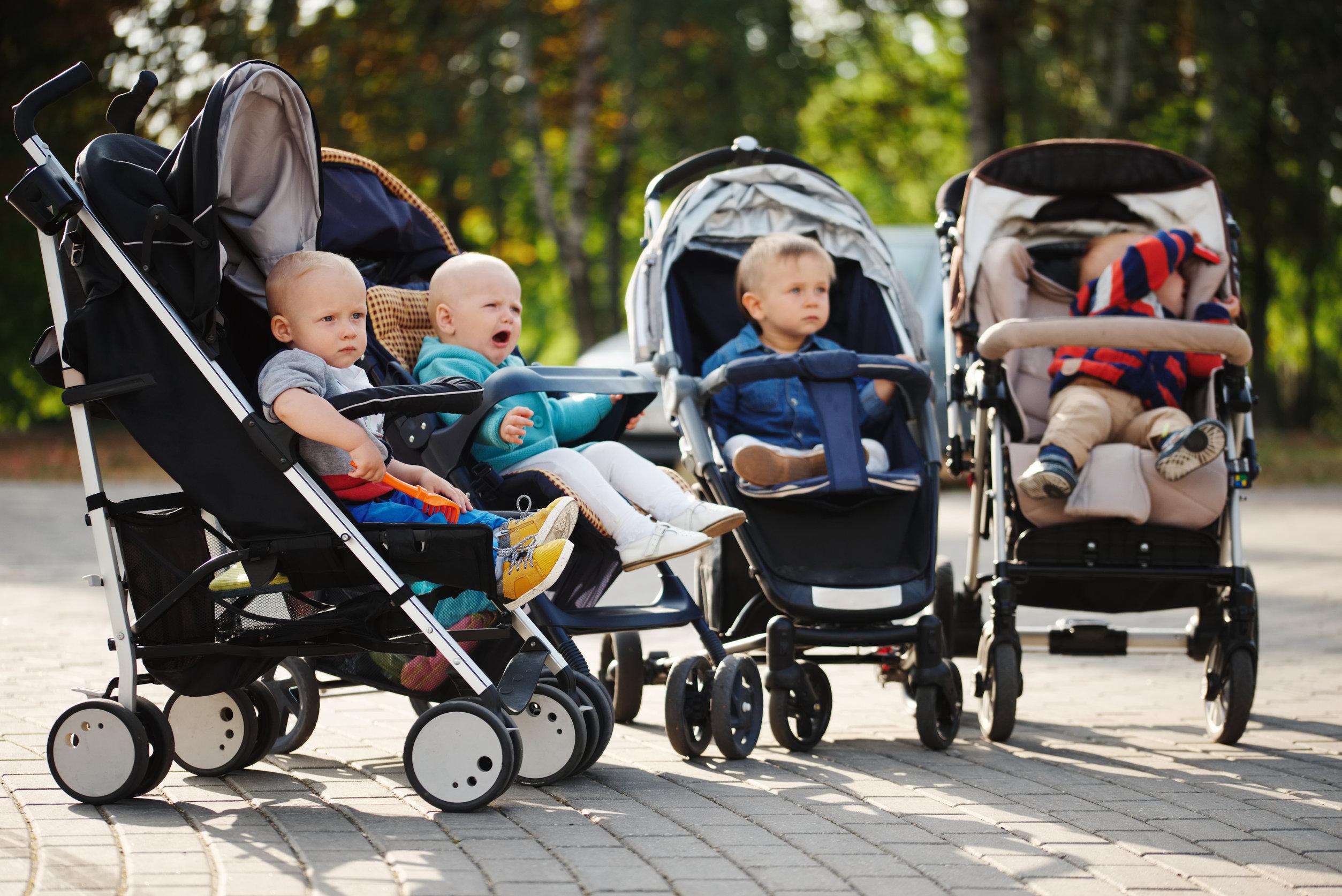crianças divertidas sentadas em carrinhos de bebé no parque